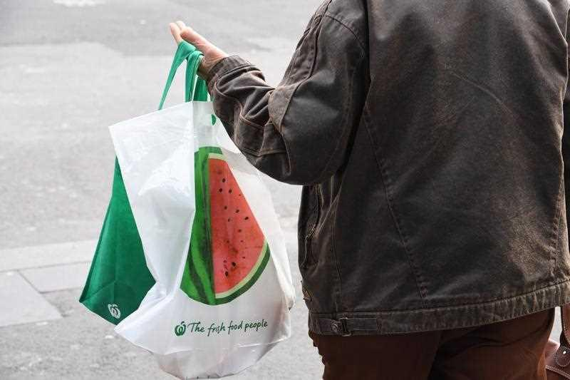 A person holds a Woolworths reusable shopping bag.