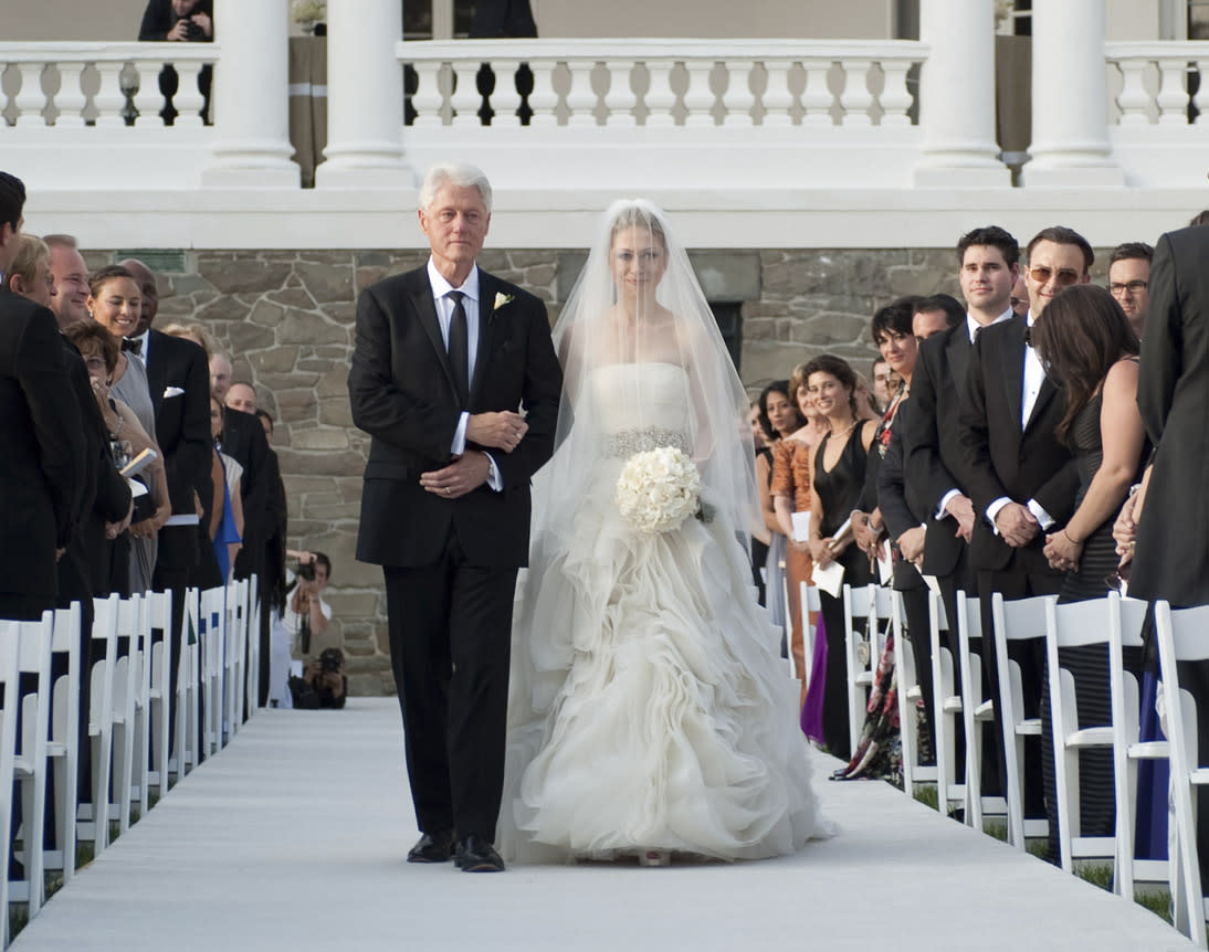 "FILE - This July 31, 2010 file photo released by Genevieve de Manio Photography shows former President Bill Clinton walking his daughter Chelsea down the isle for her wedding in Rhinebeck,N.Y. No one, including Clinton and designer Wang, expected the media circus that accompanied last year's wedding, says Darcy Miller, editor in chief of Martha Stewart Weddings, but all those photos and attention meant that a lot of gowns are coming out now that were inspired by the delicate strapless with a jeweled waistband. ""It was copied in the industry immediately. It's the classic, romantic, fairy-tale dress on a modern woman."""