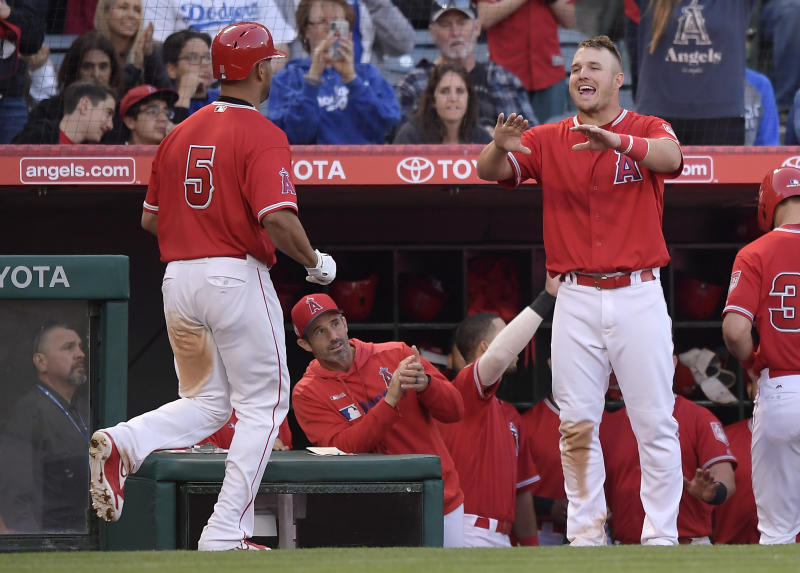 Los Angeles Angels' Albert Pujols, left, is congratulated by Mike Trout, right, as manager Brad Ausmus watches during the fourth inning of the team's preseason baseball game against the Los Angeles Dodgers on Sunday, March 24, 2019, in Anaheim, Calif. (AP Photo/Mark J. Terrill)