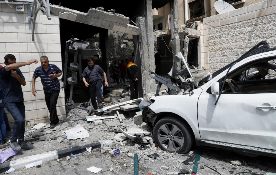People inspect destroyed cars and the rubble of residential building which was hit by Israeli airstrikes, in Gaza City, Thursday, May 20, 2021. (AP Photo/Adel Hana)