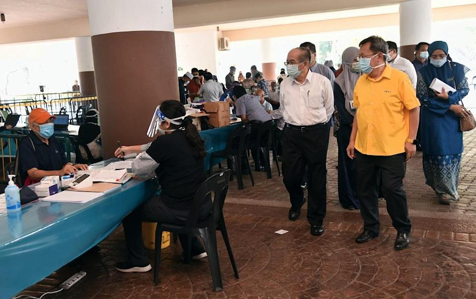 Deputy Chief Minister Datuk Amar Douglas Uggah (second, right) observing the registration process of the vaccination programme at the Indoor Stadium, April 23, 2021. ― Picture courtesy of the state Information Department