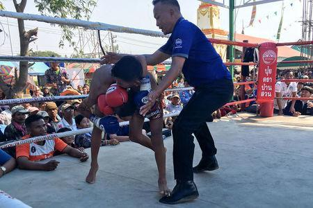 Nanthawat Pomsod, 11, who is a child boxer, fights Kritthonglek Sitkritthongkam during a boxing match at a temple in Buriram province, Thailand, February 2, 2018. REUTERS/Prapan Chankeaw