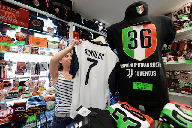 A woman adjusts a Juventus jersey with the name of Cristiano Ronaldo at a souvenir shop in Turin, Italy July 11, 2018. REUTERS/Massimo Pinca