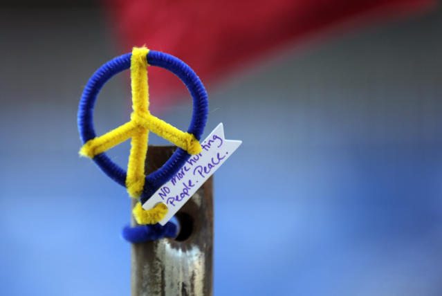 """A peace symbol bearing the words of 2013 Boston Marathon bombing victim Martin, """"No more hurting people. Peace,"""" is affixed to a pole near the finish line of the 118th Boston Marathon Monday, April 21, 2014 in Boston. (AP Photo/Charles Krupa)"""