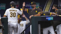 San Diego Padres' Eric Hosmer (30) is congratulated by teammates after scoring on a bases-loaded walk to Jake Cronenworth during the second inning in Game 3 of a baseball National League Division Series Thursday, Oct. 8, 2020, in Arlington, Texas. (AP Photo/Sue Ogrocki)