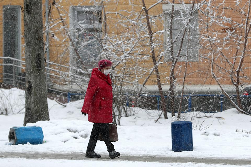 Photo shows a woman in a face mask and warm winter clothes walking in the snow in Yekaterinburg, Russia.