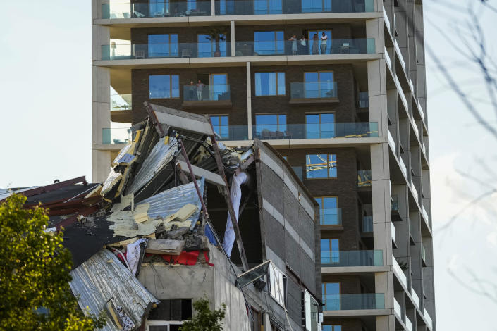 People look at the rubble of a building that partially collapsed killing one person in Antwerp, Belgium, Friday, June 18, 2021. Local police reported that one person was killed and several were injured after an under construction building and its scaffolding collapsed in a new apartment blocks area. (AP Photo/Francisco Seco)