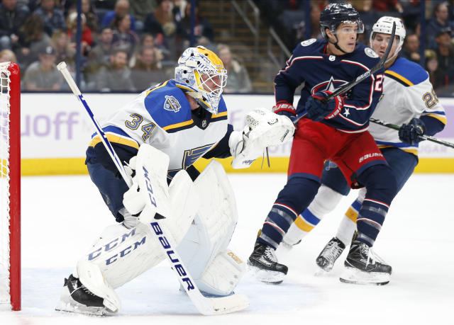 St. Louis Blues' Jake Allen, left, protects the net as teammate Mackenzie MacEachern, right, and Columbus Blue Jackets' Sonny Milano fight for position during the second period of an NHL hockey game Friday, Nov. 15, 2019, in Columbus, Ohio. (AP Photo/Jay LaPrete)