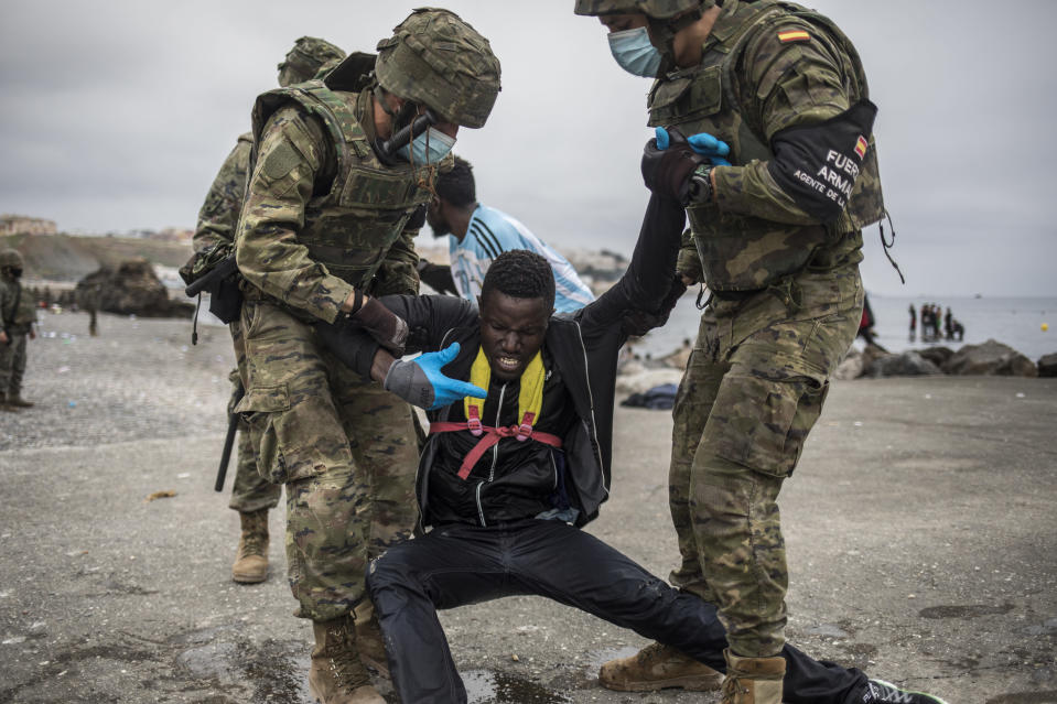 A man is held by soldiers of the Spanish Army at the border of Morocco and Spain, at the Spanish enclave of Ceuta, on Tuesday, May 18, 2021. Ceuta, a Spanish city of 85,000 in northern Africa, faces a humanitarian crisis after thousands of Moroccans took advantage of relaxed border control in their country to swim or paddle in inflatable boats into European soil. Around 6,000 people had crossed by Tuesday morning since the first arrivals began in the early hours of Monday, including 1,500 who are presumed to be teenagers. (AP Photo/Javier Fergo)