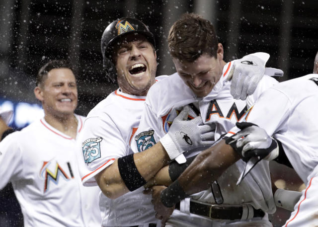 Miami Marlins' J.B. Shuck, center, celebrates with Brian Anderson, right, after Anderson hit a sacrifice fly to score Miguel Rojas during the ninth inning of a baseball game against the San Francisco Giants, Wednesday, June 13, 2018, in Miami. The Marlins won 5-4. (AP Photo/Lynne Sladky)
