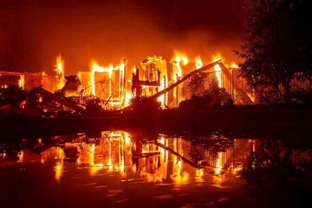 PHOTO: A burning home is reflected in a pool during the Carr fire in Redding, Calif., July 27, 2018. (Josh Edelson/AFP/Getty Images)