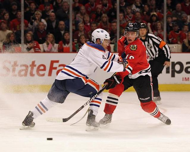 CHICAGO, IL - JANUARY 02: Jonathan Toews #19 of the Chicago Blackhawks fires a shot past Taylor Hall #4 of the Edmonton Oilers at the United Center on January 2, 2012 in Chicago, Illinois. The Oilers defeated the Blackhawks 4-3. (Photo by Jonathan Daniel/Getty Images)