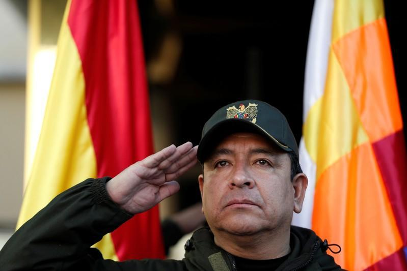 The Police Commander Vladimir Yuri Calderon salutes in front of the Wiphala and Bolivian flags during a ceremony at the General Command of the police in La Paz