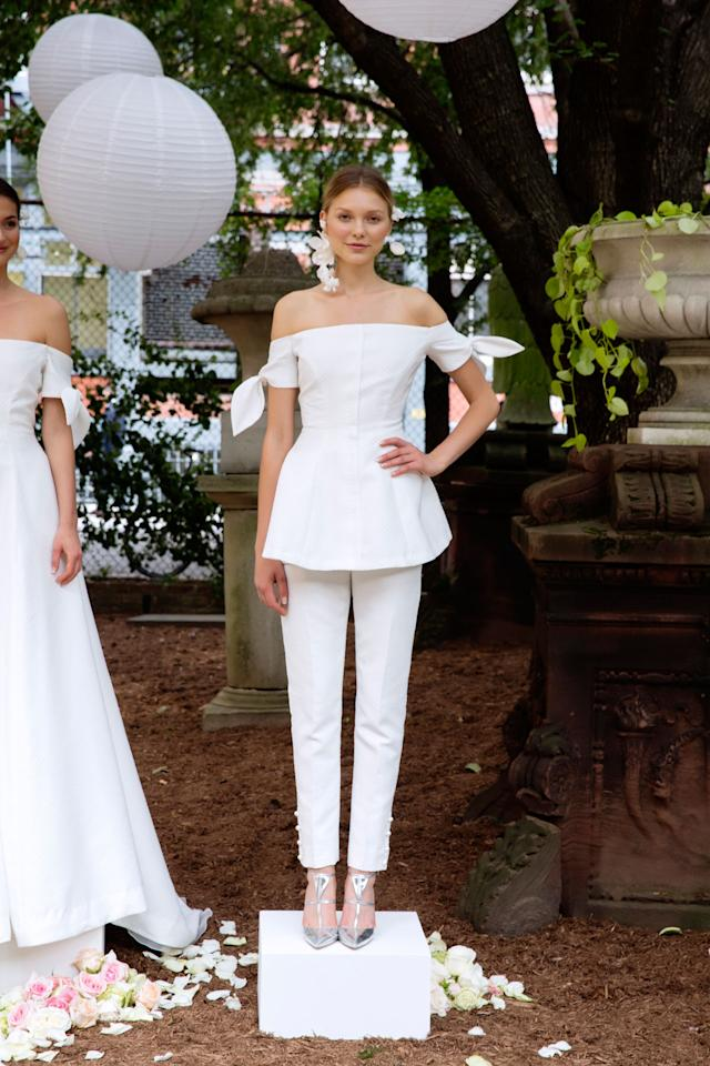 <p>A model wears a white off-the-shoulder blouser and matching pants from the Fall 2018 Bridal collection. (Photo: courtesy of Taylor Jewell, Nina Westervelt, Lela Rose) </p>