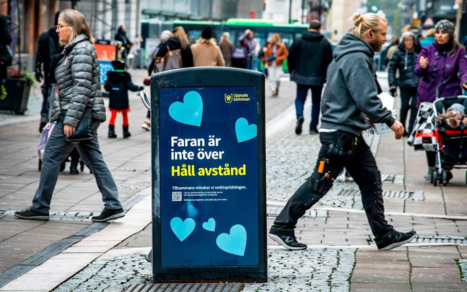 """People walk past a bin with a sign reading """"The danger is not over - Keep your distance"""" in a pedestrian street in central Uppsala, the first town in Sweden to enter local restrictions - CLAUDIO BRESCIANI/AFP"""