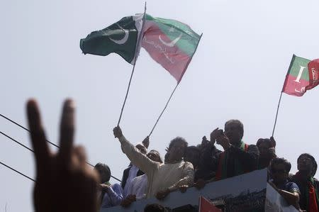 Imran Khan, chairman of Pakistan Tehreek-e-Insaf (PTI) political party, waves a national flag from a truck as he leads the Freedom March in Lahore August 14, 2014. REUTERS/Akhtar Soomro