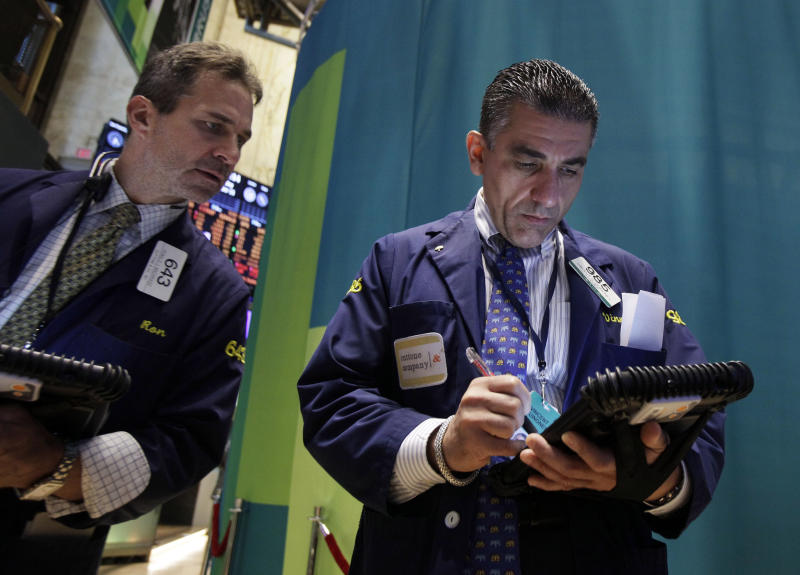 Traders Ronald Madarasz, left, and Vincent Quinones work on the floor of the New York Stock Exchange Monday, Oct. 15, 2012.  Stocks opened higher Monday on Wall Street after a strong report on retail sales. (AP Photo/Richard Drew)