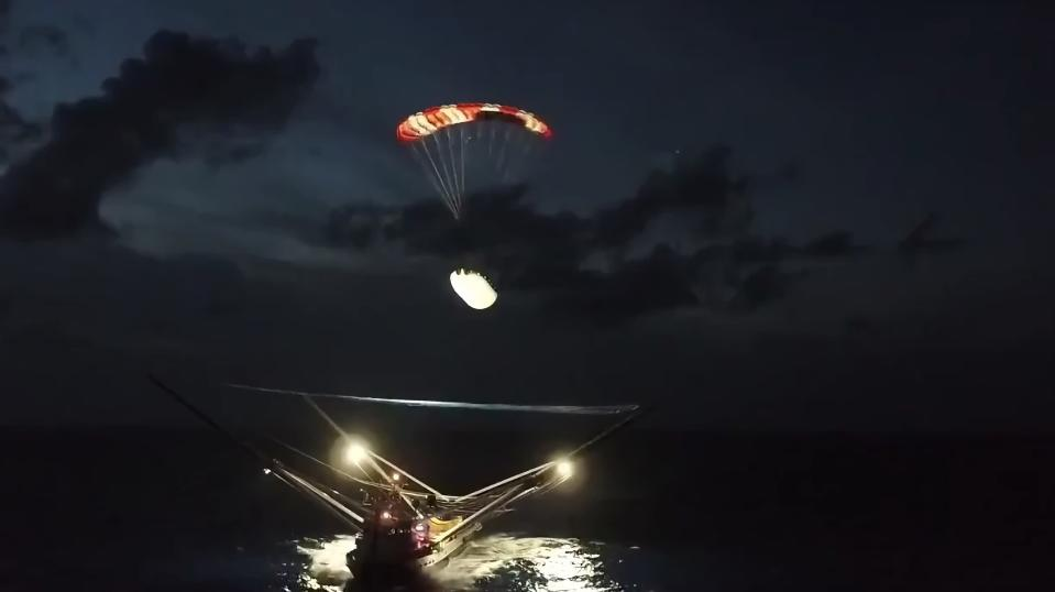 SpaceX's Ms. Tree recovery ship catching a falling Falcon 9 fairing in 2019.