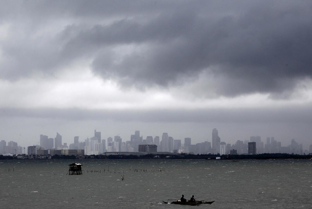 Fishermen ride on their boat as dark clouds loom over the city brought by Super Typhoon Usagi in Navotas City, metro Manila September 21, 2013. The year's most powerful typhoon slammed into the Philippines' northernmost islands on Saturday, cutting communication and power lines, triggering landslides and inundating rice fields, officials said. Packing winds of 185 kph (114 mph) near the center and gusts of up to 220 kph, Typhoon Usagi weakened after hitting the Batanes island group, and is moving slowly west-northwest at 19 kph towards southern China, the weather bureau said. REUTERS/Romeo Ranoco (PHILIPPINES - Tags: DISASTER SOCIETY ENVIRONMENT CITYSCAPE)