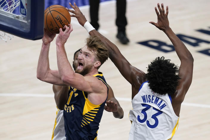 Indiana Pacers' Domantas Sabonis (11) shoots next to Golden State Warriors' James Wiseman (33) during the first half of an NBA basketball game Wednesday, Feb. 24, 2021, in Indianapolis. (AP Photo/Darron Cummings)