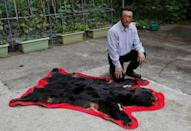 Apple farmer Satomi Ito, 66, poses next to a fur of a wild bear which he hunted before at his home in Kitaakita, Akita prefecture, northern Japan June 21, 2018. Picture taken June 21, 2018. REUTERS/Kiyoshi Takenaka