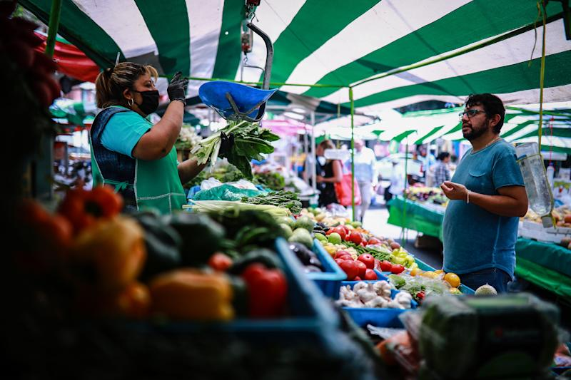 MEXICO CITY, MEXICO - APRIL 17: Rosa Mar'a attends a customer at her mobile vegetable stand on April 17, 2020 in Mexico City, Mexico. Mexico is under health emergency, which implies that only essential activities are permitted. Government suggested population to stay at home but quarantine is not obligatory as there is major concern about the economic activity. Hugo Lopez-Gatell Undersecretary of Prevention and Health Promotion announced the extension of the measures until at least, May 30 in those cities with a bigger risk and number of contagion. (Photo by Manuel Velasquez/Getty Images)