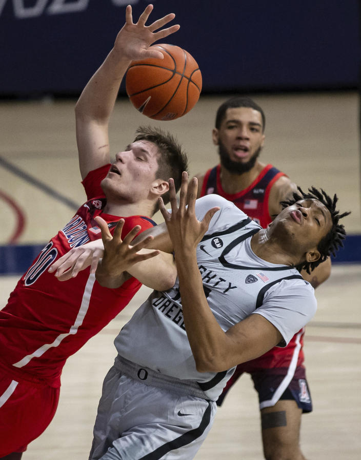 Arizona forward Azuolas Tubelis (10) and Oregon forward Chandler Lawson (13) collide while trying to grab a rebound during an NCAA college basketball game, Saturday, Feb. 13, 2021, in Tucson, Ariz. (Josh Galemore/Arizona Daily Star via AP)