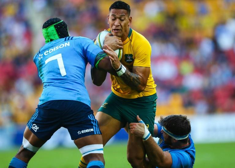 Israel Folau (C) of Australia is tackled by Italy's Maxime Mbandao (L) and Marco Fuser during their rugby union Test match at Suncorp Stadium in Brisbane on June 24, 2017