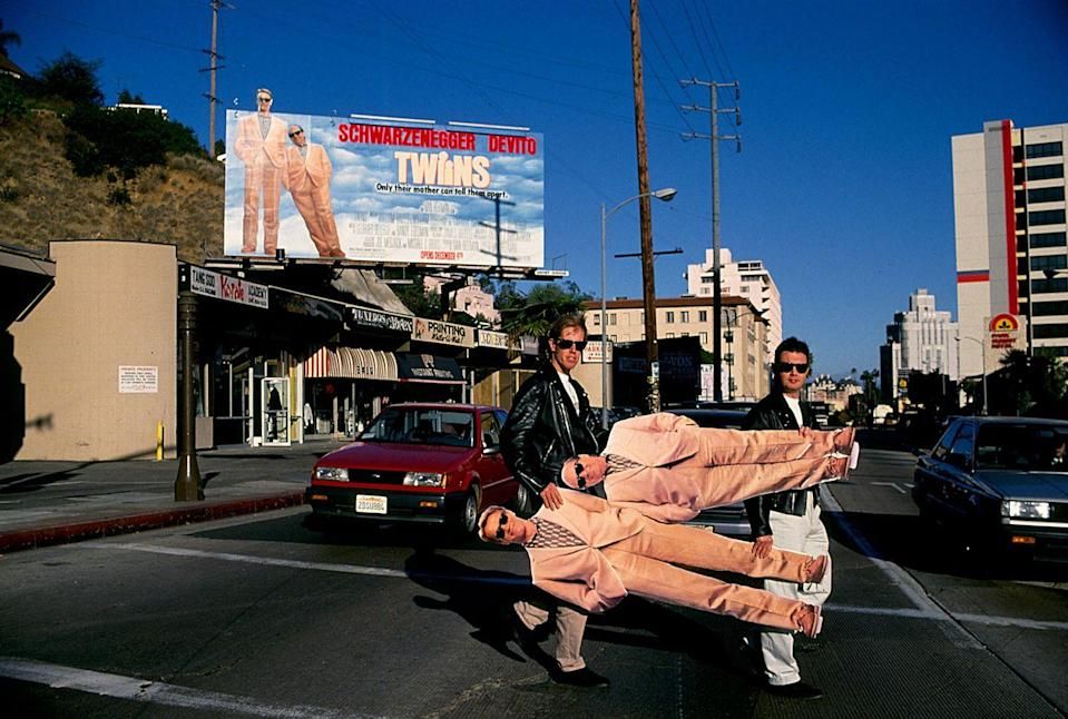 <p>English writers William Davis and William Osborne, known as the two Wills and the writers of the Blockbuster hit <em>Twins</em>, carry life-size cutouts of the film's two lead actors — Arnold Schwarzenegger and Danny Devito — across Sunset Boulevard.</p>