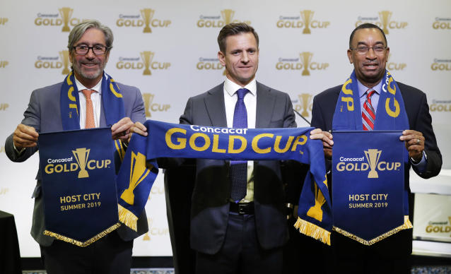Tom Murray, CEO of Charlotte Regional Visitors Authority, left, Manolo Zubiria, Concacaf chief of football officer, center, and Charlotte City council member James Mitchell, right, pose for a photo during a new conference to announce Charlotte, N.C. as one of the sites for the 2019 Concacaf Gold Cup soccer tournament in Charlotte, N.C., Tuesday, May 15, 2018. (AP Photo/Chuck Burton)