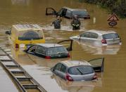 FILE - In this file photo dated Saturday, July 17, 2021, people check for victims in flooded cars on a road in Erftstadt, Germany, following heavy rainfall that broke the banks of the Erft river, causing massive damage. Scientists say global warming makes the kind of extreme rainfall that caused deadly flash floods in western Europe last month more likely, though it remains unclear exactly how much. (AP Photo/Michael Probst, FILE)