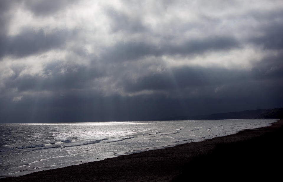 In this May 2, 2019, photo, the sun shines through storm clouds on Omaha Beach in St. Laurent-sur-Mer, Normandy, France. Allied troops first landed on Normandy's beaches on June 6, 1944, to begin the liberation of Europe from years of Nazi occupation. (AP Photo/Virginia Mayo)