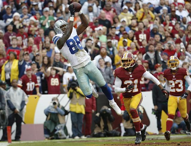 Dallas Cowboys wide receiver Dez Bryant pulls in a touchdown pass next to Washington Redskins strong safety Brandon Meriweather during the first half of an NFL football game in Landover, Md., Sunday, Dec. 22, 2013. (AP Photo/Alex Brandon)