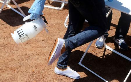A World Health Organization (WHO) worker sprays her shoes with chlorine as she prepares a centre for vaccination during the launch of a campaign aimed at beating an outbreak of Ebola in the port city of Mbandaka, Democratic Republic of Congo May 21, 2018. REUTERS/Kenny Katombe