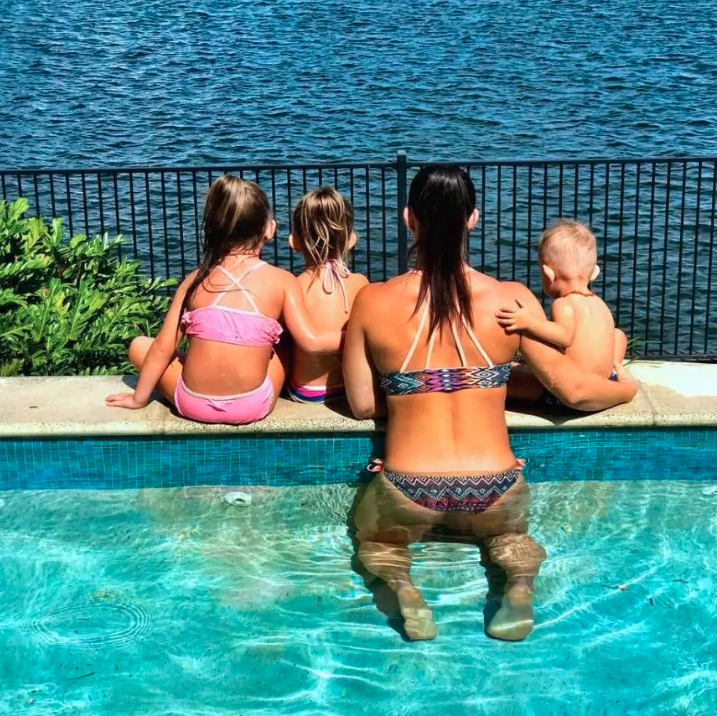 Hannah Clarke and her three children staring into the ocean as they lie in the pool