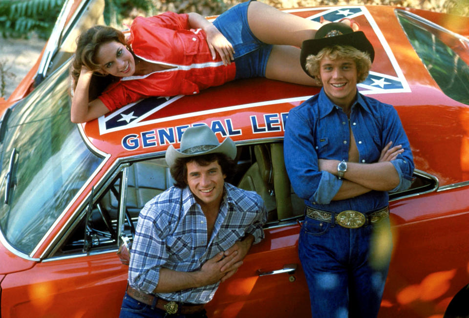 From left to right: Catherine Bach, Tom Wopat and John Schneider pose alongside the General Lee featured in 'The Dukes of Hazzard' (CBS / Courtesy: Everett Collection)