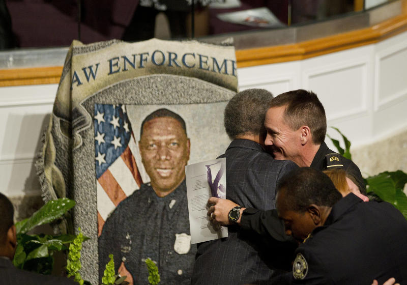 Mourners embrace during a memorial service for Atlanta Police helicopter pilot Richard J. Halford Friday, Nov. 9, 2012 in Atlanta. Halford was one of two officers killed last Saturday night in a helicopter crasher while assisting in a search for a missing child. (AP Photo/John Bazemore)
