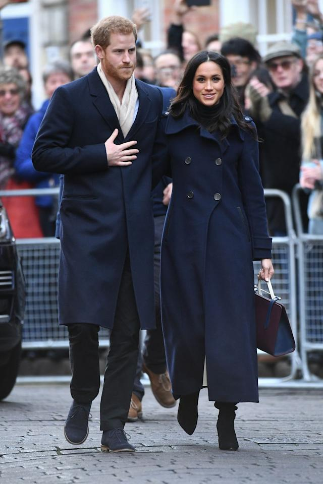 """<p>For her first official royal engagement, Meghan chose a navy blue, double-breasted coat from the <a href=""""https://www.mackage.com/elodie-double-buttoned-tailored-flat-wool-coat/ELODIE.html?dwvar_ELODIE_color=COL540&cgid=women-wool-coats#start=1&cgid=women-wool-coats"""" target=""""_blank"""">Canadian line Mackage</a> over a black turtleneck, tan skirt, and color-blocked handbag from <a href=""""https://www.strathberry.com/collections/the-strathberry-midi-tote/products/the-strathberry-midi-tote-tri-colour-burgundy-navy-vanilla?"""" target=""""_blank"""">Scottish brand Strathberry</a>.</p>"""
