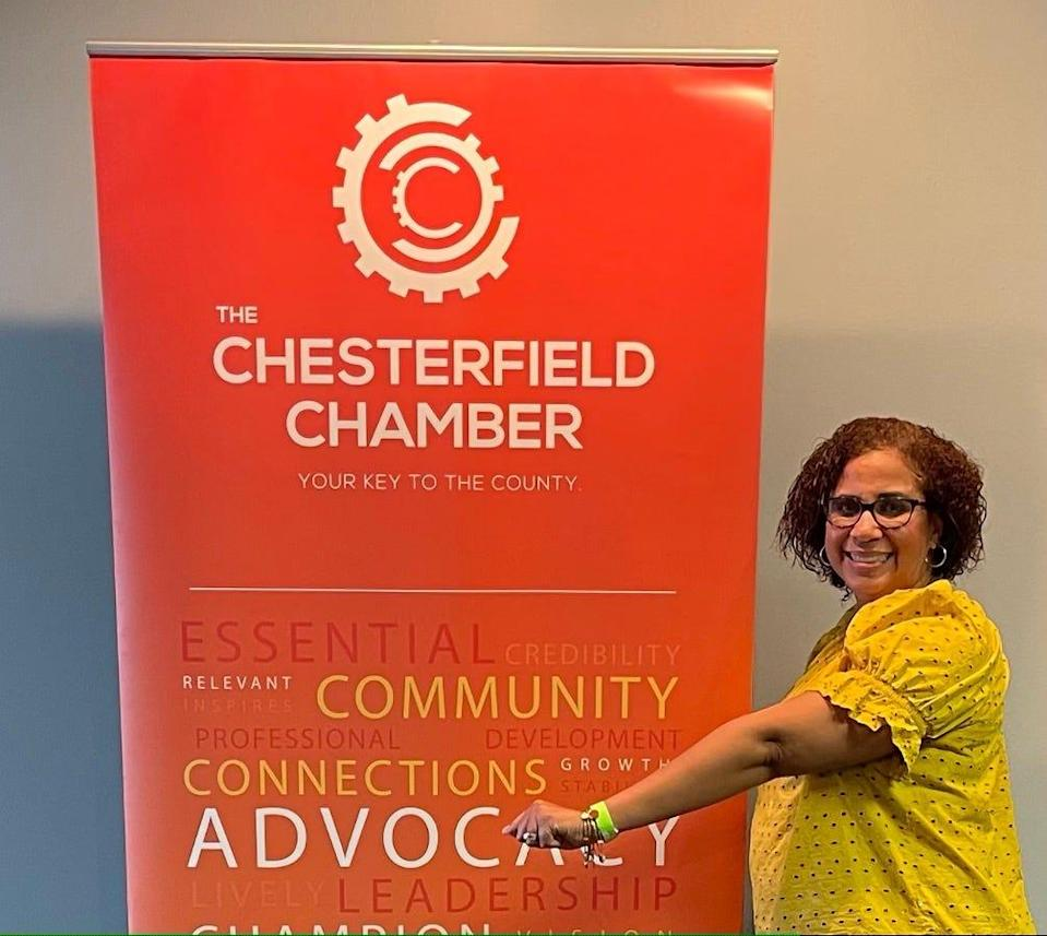 Danielle Fitz-Hugh, president of the Chesterfield Chamber of Commerce in Virginia, shows off one of the green wrist bands meeting attendees often wear to indicate they are vaccinated and open for handshakes.