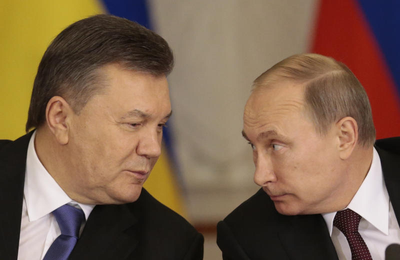 """FILE - In this Tuesday Dec. 17, 2013 file photo, Russian President Vladimir Putin, right, and his Ukrainian counterpart Viktor Yanukovych talk during a news conference in Moscow. Moscow on Wednesday granted Ukrainian President Viktor Yanukovych protection """"on the territory of Russia,"""" shortly after the fugitive leader sought help from the Kremlin, according to an official quoted by Russian news agencies. (AP Photo/Ivan Sekretarev, file)"""