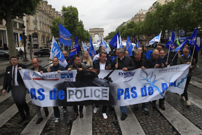 """French police unionists demonstrate with a banner reading"""" No police, no peace"""" down the Champs-Elysee avenue, Friday, June 12, 2020 in Paris. French police are protesting a new ban on chokeholds and limits to what they can do during arrests, part of government efforts to stem police brutality and racism in the wake of global protests over George Floyd's death in the U.S. (AP Photo/Michel Euler)"""