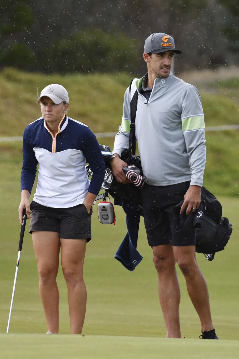 Australian cricket player Mitchell Starc, right, walks the fairway with his wife, Alyssa Healy, at the Grange Golf Club in Adelaide, Australia on Feb. 13, 2019. Starc hasn't picked up a cricket bat or ball in two months, and isn't exactly salivating at the prospect of going back to work. (David Mariuz/AAP Image via AP)