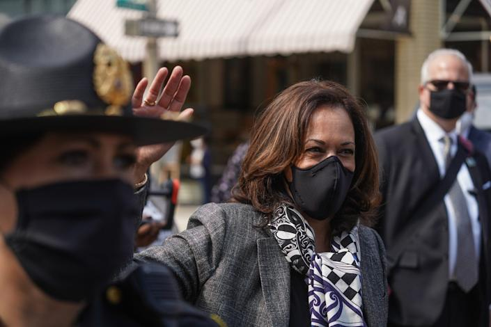 U.S. Senator and Democratic Vice Presidential nominee Kamala Harris waves to supporters while walking to talk with small business owners in downtown Flint on September 22, 2020, during a campaign stop in Michigan.
