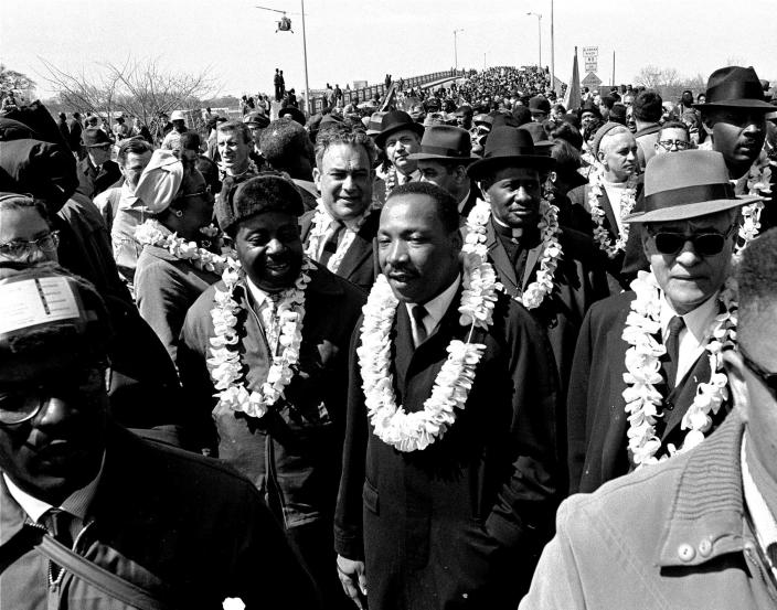"""FILE - In this March 21, 1965 file photo, Martin Luther King, Jr. and his civil rights marchers cross the Edmund Pettus Bridge in Selma, Ala., heading for the capitol, Montgomery, during a five day, 50 mile walk to protest voting laws. The annual celebration of the Martin Luther King Jr. holiday in his hometown in Atlanta is calling for renewed dedication to nonviolence following a turbulent year. The slain civil rights leader's daughter, the Rev. Bernice King, said in an online church service Monday, Jan. 18, 2021, that physical violence and hateful speech are """"out of control"""" in the aftermath of a divisive election followed by a deadly siege on the U.S. Capitol in Washington by supporters of President Donald Trump. (AP Photo/File)"""