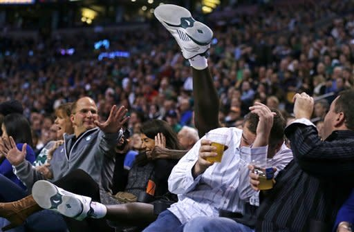 Boston Celtics forward Kevin Garnett's feet fly over the first row as he lands in the second row while chasing the loose ball against the Indiana Pacers during the second quarter of an NBA basketball game in Boston, Friday, Jan. 4, 2013. (AP Photo/Charles Krupa)