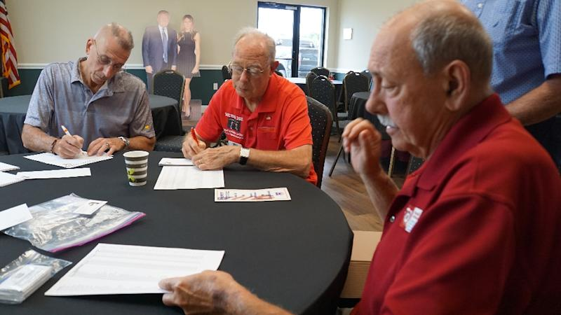 Retirees Ronald McMahan (R), Don Eaton (C) and Andy Bilardello, all leaders of local Republican clubs, address envelopes inviting new residents to join the clubs in The Villages, Florida; all are supporters of US President Donald Trump (AFP Photo/Leila MACOR)