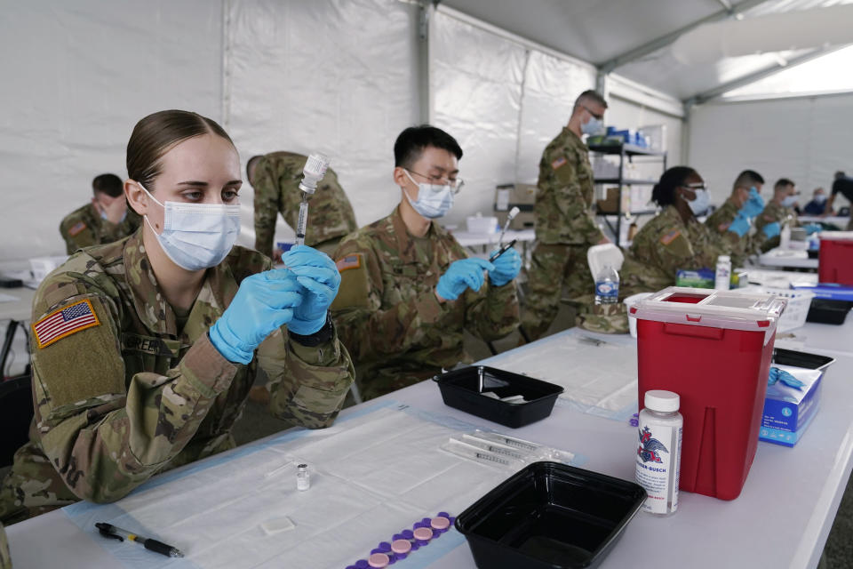 FILE - In this March 9, 2021, file photo, Army health specialists fill syringes with the Pfizer COVID-19 vaccine in Miami. Despite the clamor to speed up the U.S. vaccination drive against COVID-19, the first three months of the rollout suggest faster is not necessarily better. (AP Photo/Marta Lavandier, File)