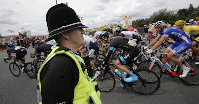 Britain's Christopher Froome, center right with race number one, passes a police officer during the second stage of the Tour de France cycling race over 201 kilometers (124.9 miles) with start in York and finish in Sheffield, England, Sunday, July 6, 2014. (AP Photo/Christophe Ena)