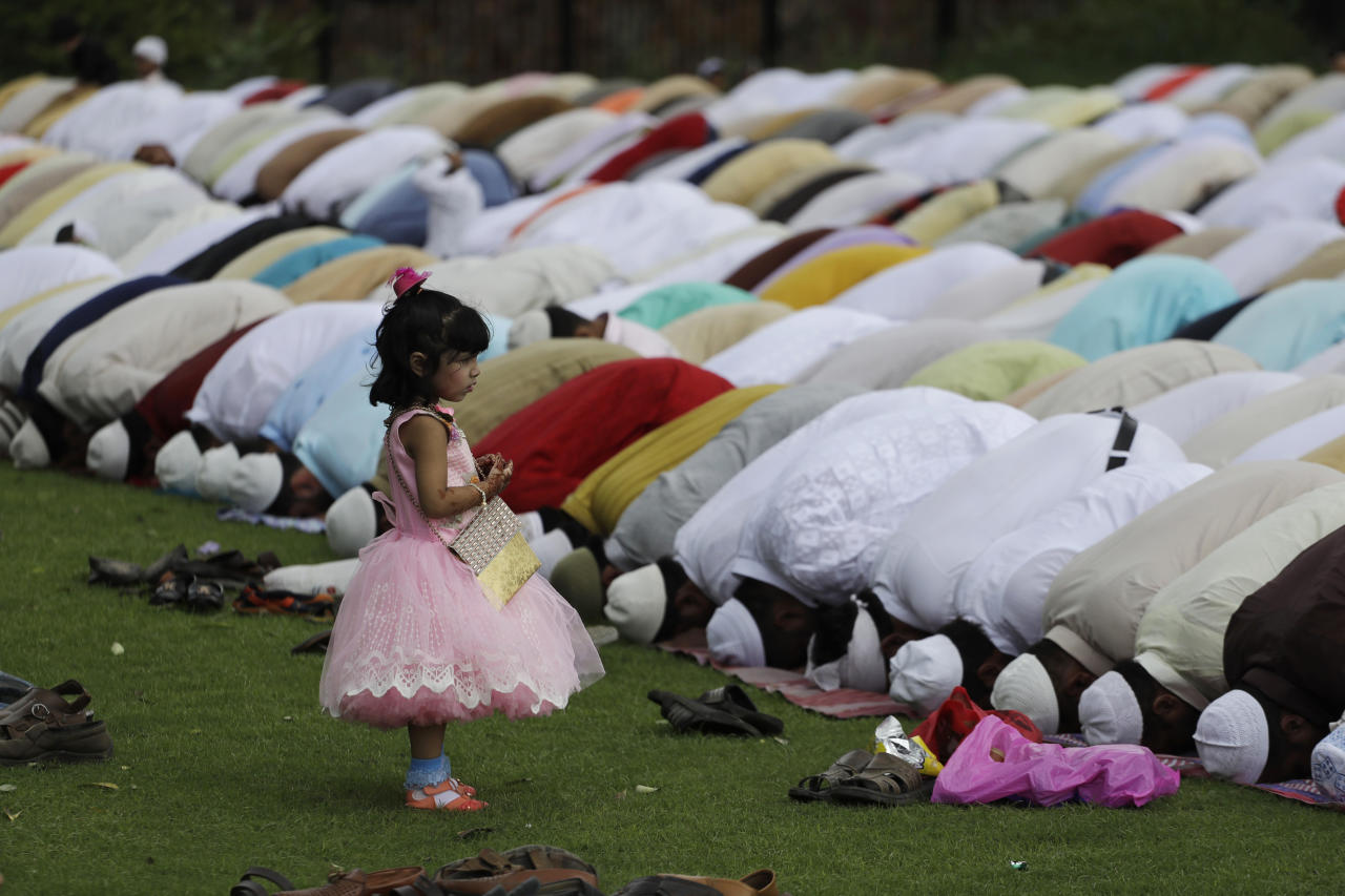 <p>An Indian Muslim girl watches elders offer Eid al-Adha prayers at the 14th century Feroz Shah Kotla Jami Mosque in New Delhi, India, Saturday, Sept. 2, 2017. (Photo: Tsering Topgyal/AP) </p>