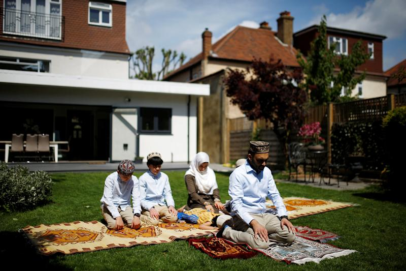 Image: Farood Ahmed and his wife, Sana, pray with their children Zaine, Rayan, Usman and Inaya in their garden to mark the end of Ramadan in Surbiton, London, on May 24, 2020. (Henry Nicholls / Reuters)